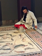 She is cleaning an ancient floor mosaic.